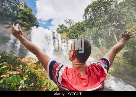 Happy young man (traveler) standing near Wachirathan waterfall in tropical rainforest. Chiang Mai Province, Thailand - Stock Photo