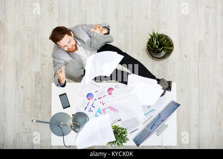 Cheerful bearded entrepreneur sitting at office desk and throwing documents in air after successful completion of - Stock Photo