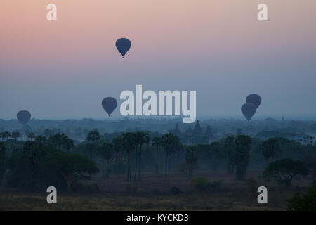 Silhouette of ancient temples and pagodas and several hot-air balloons above the ancient plain of Bagan in Myanmar - Stock Photo