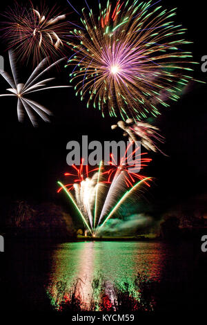 Colourful Wiltshire Fireworks display with reflections off a lake - Stock Photo