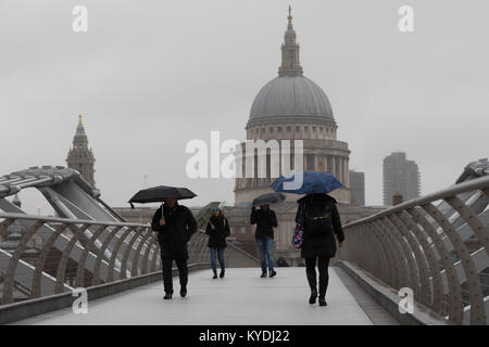 London, UK. 15th Jan, 2018. People with umbrellas walk across Millennium Bridge in London during wet weather today. - Stock Photo