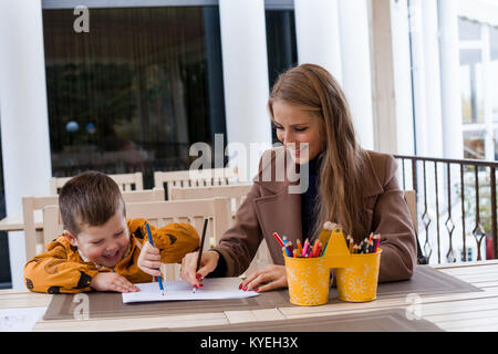 woman teaches the boy to draw with colored pencils - Stock Photo