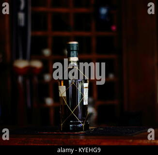 Bottle of golden liquor on a bar counter - image with copy space - Stock Photo