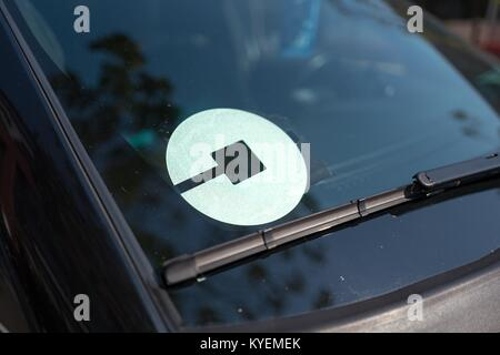 Logo for car-sharing company Uber on the passenger side windshield of a vehicle in the South of Market (SoMa) neighborhood - Stock Photo