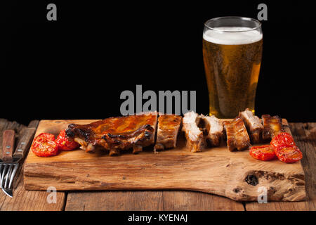 Pork ribs in barbecue sauce and honey baked tomatoes on the old wooden table. Meats and light beer on black background - Stock Photo