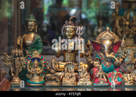 Statues of Indian hindu gods shiva, ganesha, buddha, devi,  made out of brass and colored green and pink, in several - Stock Photo