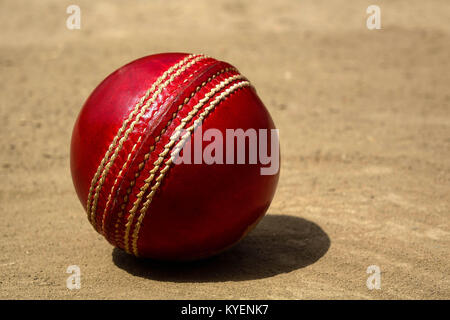 A brand new red Cricket ball with white stitches in pitch - Stock Photo