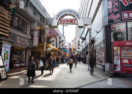 People walk down the Ameyoko Shopping Street (aka Ameya-Yokocho), a popular outdoor market area in the Taito ward - Stock Photo
