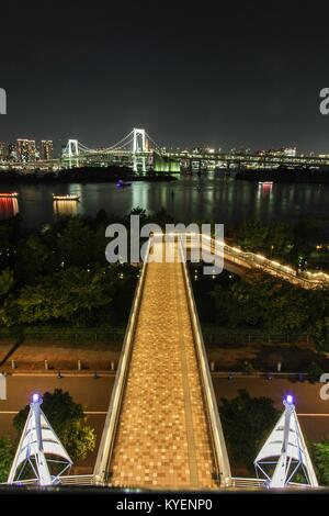 Night view of urban skyline, including rainbow bridge and Odaiba, a shopping district on a man-made island in Tokyo - Stock Photo