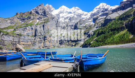Sunny Summer Activities and recreation, rowing blue boats while enjoying beautiful Swiss alps view on Lake Oeschinen - Stock Photo