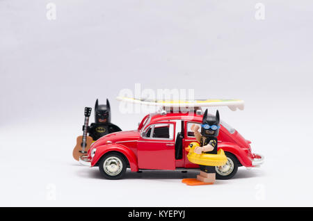 lego batman and vacation batman going on holiday with volkswagen car isolated on white. - Stock Photo