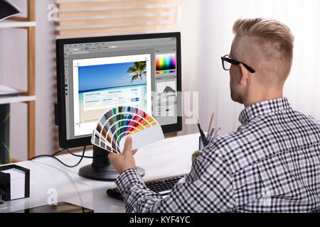 A Male Designer Using Computer While Holding Color Swatches In His Hand - Stock Photo