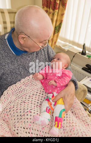 New born baby sitting on her great grandfather's lap, looking up at him - Stock Photo