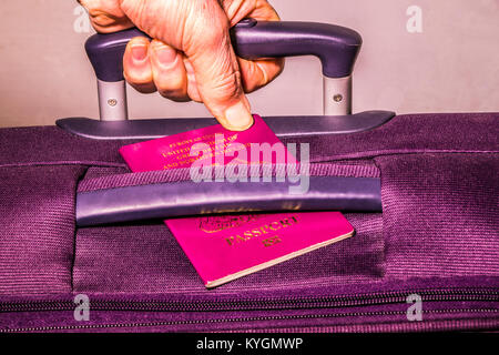 Man's hand holding a suitcase handle with a thumb securing a UK passport showing: European Union United Kingdom - Stock Photo