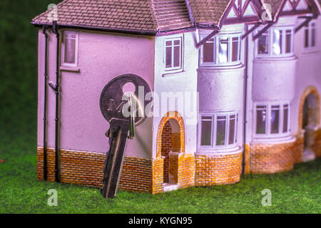Key to the door leaning on a model house. Concept relating to home occupation, eg, buying / selling / renting / - Stock Photo