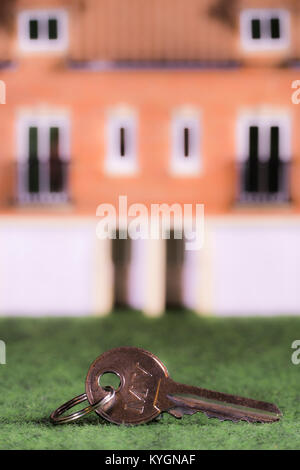 Key to the door in focus with defocused model house behind. Concept relating to home occupation, eg, buying / selling / renting / moving / mortgage.
