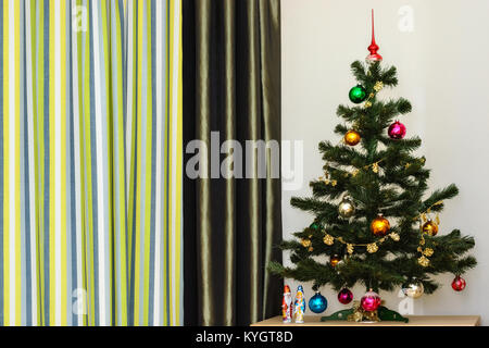 Christmas tree decorated with toys against the wall and striped curtains. - Stock Photo