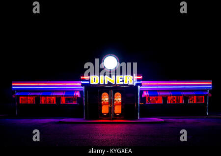 A traditional American Diner at night with a large sign and clorful luminous, fluourescent and neon lighting that - Stock Photo