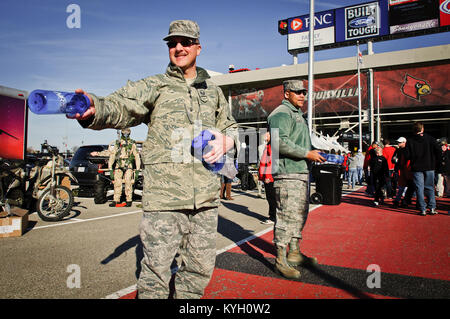 Master Sgt. Ted Bothur, a recruiter with the Kentucky Air National Guard, hands out water bottles to fans entering - Stock Photo