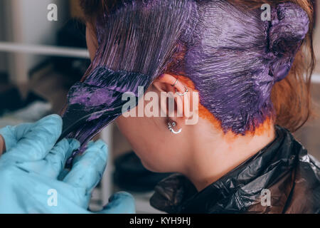 Professional hairdresser dyeing hair of her client in salon. Selective focus. - Stock Photo