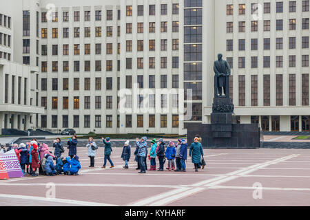 Children posing at the Independence Square, in front of the Lenin monument and the House of Government as background. - Stock Photo