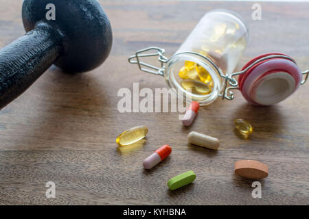 Closeup on dumbbell and dietary supplements on wooden table: fitness and weight loss concept. - Stock Photo