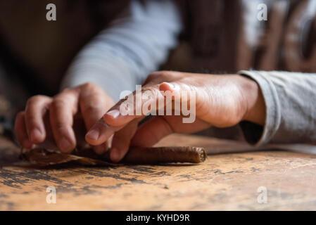 Tobacco farmer rolling cigar