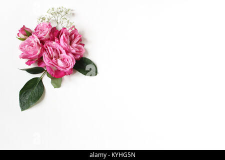 Decorative floral composition with pink roses, green leaves and and baby's breath Gypsophila flowers on white table - Stock Photo