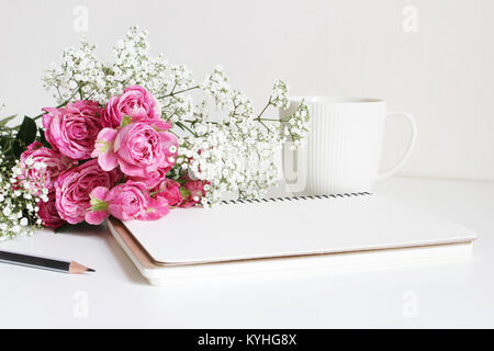 Wedding styled stock photo. Still life with pink roses, baby's breath Gypsophila flowers, white cup, pencil and - Stock Photo