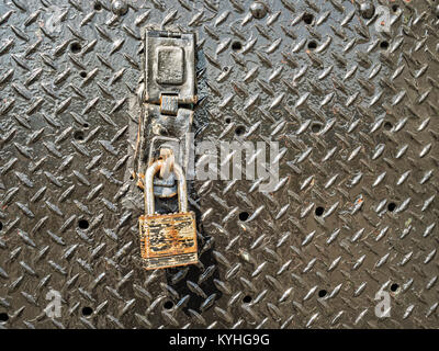 Old rusty iron padlock on metal door as symbol of safety security protection, secure data idea or rusted lock rust - Stock Photo