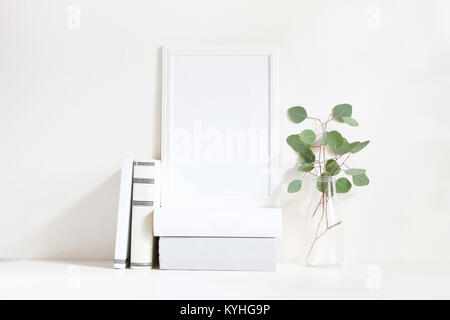 White blank wooden frame mockup with a green eucalyptus branches in glass bottle and pile of books lying on the - Stock Photo