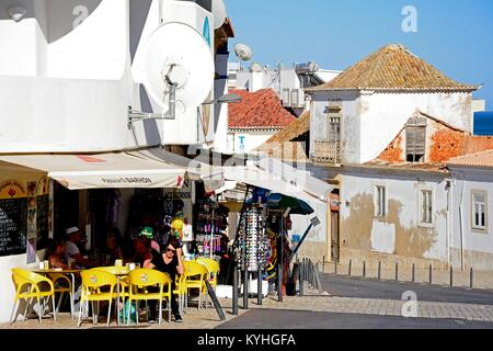 Tourists relaxing at a bar with tourists shops to the rear in the old town, Albufeira, Algarve, Portugal, Europe. - Stock Photo