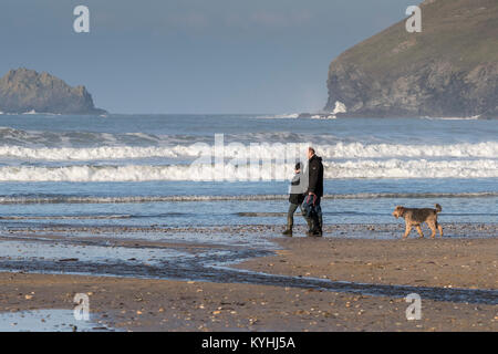 Dog walking on a beach - Dog walkers on Polzeath Beach on the North Cornwall Coast. - Stock Photo