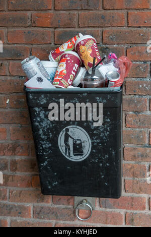 Discarded coffee cups and drinks cans in rubbish bin - Stock Photo