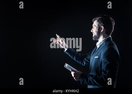 Delighted handsome businessman looking at the virtual panel - Stock Photo