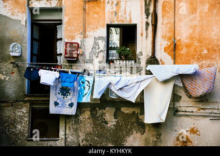 clothes hanging in some clothes lines outdoors in an old building, in the old town of Cagliari, in Sardinia, Italy - Stock Photo