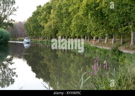 View off river in france with boy cycling on tow path with avenue of trees and motor launch in distance - Stock Photo