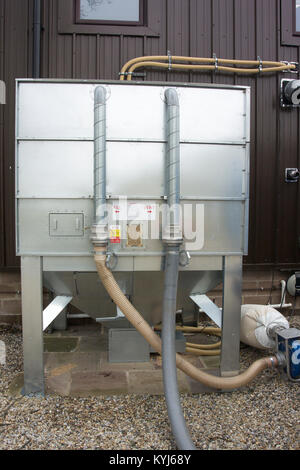 Wood pellets being delivered into a bulk hopper for use in Bio Fuel heater at an industrial park, UK. - Stock Photo