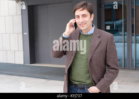 Man holding smartphone and having a conversation - Stock Photo