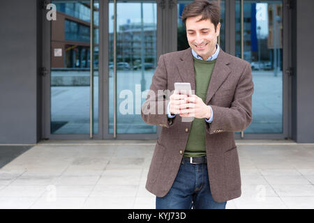Man texting a message on his smartphone - Stock Photo