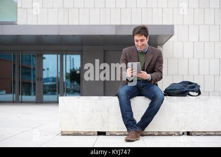 Caucasian businessman texting on digital tablet - Stock Photo