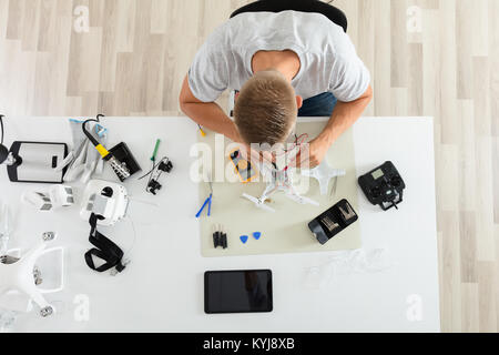 Close-up Of A Man Testing Electric Current Of Disassembled Drone Using Multimeter Tool - Stock Photo