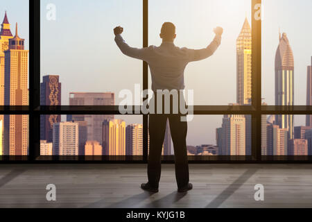 Rear View Of A Businessman Looking Out Of A Window At The City Skyline - Stock Photo