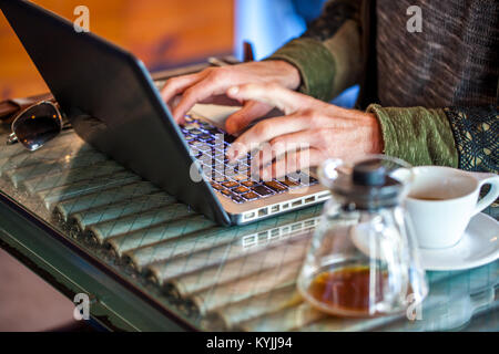 Caucasian man's hands type on laptop  with coffee mug and coffee cup next to him in a coffee shop with focus on - Stock Photo