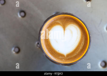 Top view of cortado coffee in a glass with the foam in shape of heart - Stock Photo
