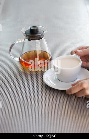 Caucasian woman hands hold ceramic cup with black tea and milk, glass teapot in background over metallic table - Stock Photo