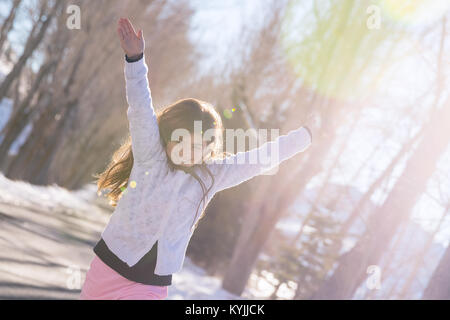 Beautiful smiling schoolgirl with raised up hands enjoying warm sunny weather in wintertime in the park, happy winter - Stock Photo