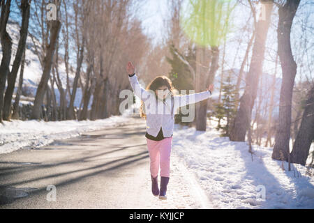 Happy girl runs and jumps up from happiness, beautiful smiling schoolgirl with raised up hands enjoying warm sunny - Stock Photo