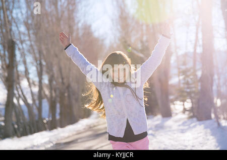 Beautiful smiling schoolgirl with raised up hands enjoying warm sunny weather in the wintertime in the park, happy - Stock Photo