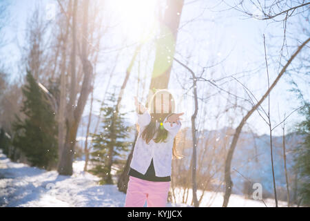 Little girl catching snowflakes in winter park, happy active child, having fun outdoors in bright sunny day, enjoying - Stock Photo